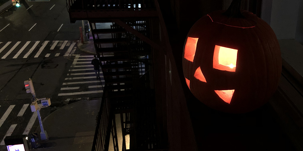 Pumpkin Jack O' Lantern above the city streets of New York City.