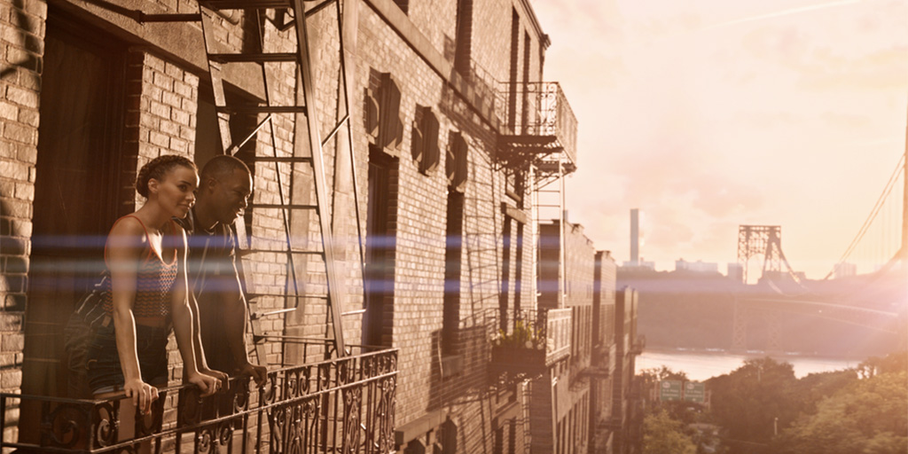 Image from In The Heights movie. Leslie Grace and Corey Hawkins standing on a fire escape with the GWB in the background.